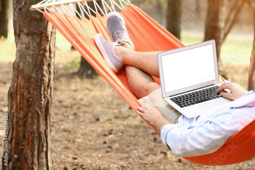 Fotografie, Obraz Young man with laptop relaxing in hammock outdoors