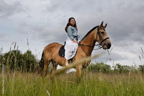 Fototapeta Young cow girl walking horse in green field