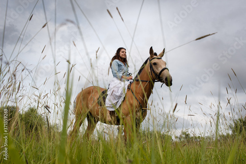 Fotografie, Obraz Young cow girl walking horse in green field