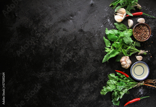 Leinwand Poster Aromatic fresh herbs and spices on a black slate, stone or concrete background
