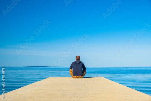 Photographie Man in hoodie and short cargo sitting on the edge of dock and meditating