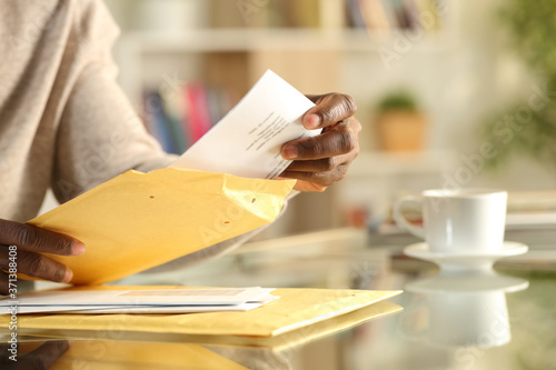 Vászonkép Black man hands opens a padded envelope sitting at home