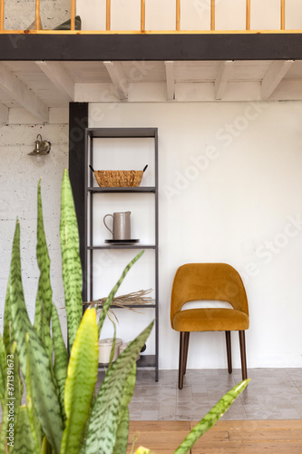 Fotomural Shelves with decorations and comfortable chair placed under mezzanine in stylish