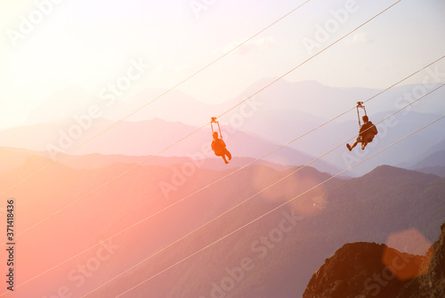 man on zip line. extreme sport in mountains at the sunset Billede på lærred