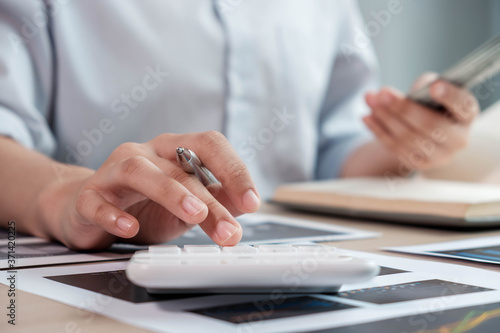 businesswoman or an accountant uses a calculator to calculate prices. And customer proposals for future financial spending for balance and prosperity, using graphs to analyze