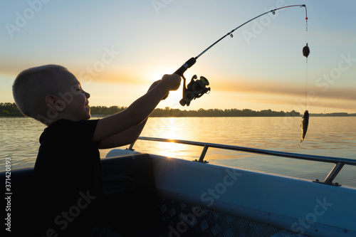 Fotografie, Obraz A boy on a fishing trip caught a fish