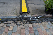 Temporary Cable Route On The Street. The Cyclist Is Out Of Focus.