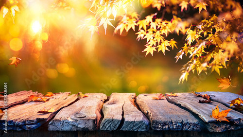Obraz Wooden Table With Red And Yellow Leaves At Sunset - Autumn Background  - fototapety do salonu
