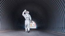 Low Angle Shot Of A Confident Handsome Astronaut Walking Towards The Camera In A Metal Tube Tunnel. Man In Futuristic Suit With Technological Panel On His Hand.