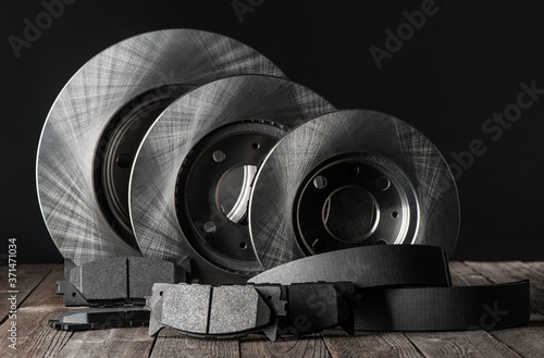 Canvas Print Row of brake discs and friction pads on rustic wooden table