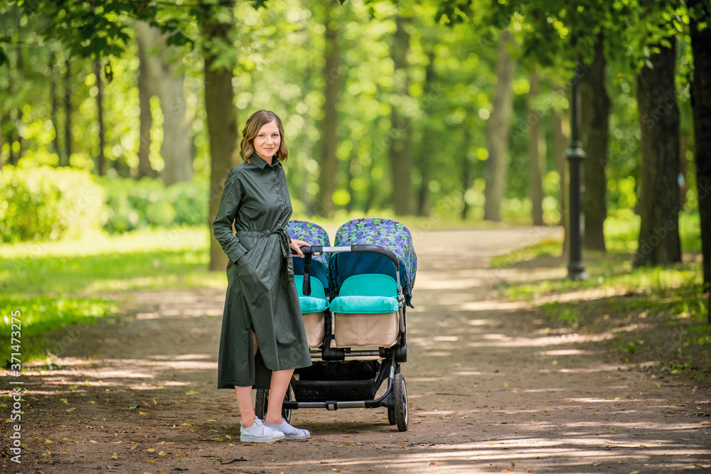Fototapeta Happy young mom walks in the park in the summer with a stroller for twins.