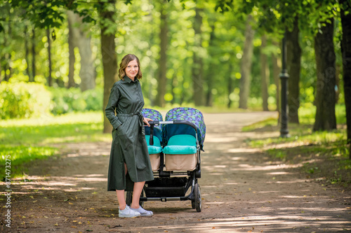Obraz Happy young mom walks in the park in the summer with a stroller for twins. - fototapety do salonu