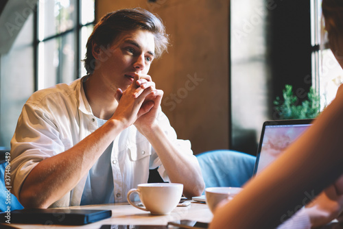 Photo Concentrated male journalist listening carefully interlocutor during friendly conversation in cafeteria