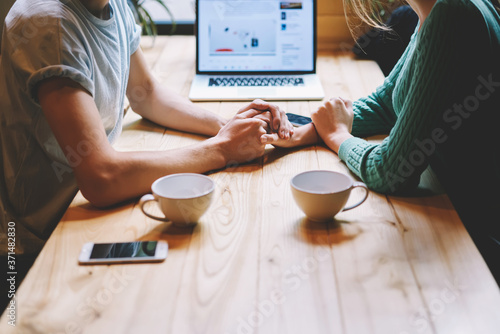 Cropped image of male and female hands holding each other sitting at wooden table with laptop computer Fotobehang