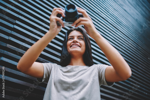 Fotomural Happy smiling female amatour photographer 20 years old checking photos on vintag