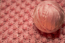Ball Of Pink Yarn With Textured Pink Background Consisting Of Pink Yarn Crocheted Baby Blanket In The Bobble Stitch Also Know As The Pineapple Stitch