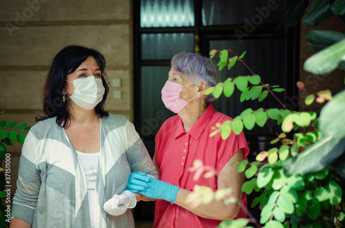 Two neighbors in protective masks and rubber gloves have just left the entrance of the house Canvas Print