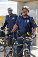 Portrait Of Bicycle Police Officers Standing Outside With Their Bikes Looking Towards Camera Smiling