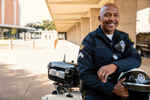 Portrait Of Police Officer Sitting On His Motorcycle Outside Looking Towards Camera Smiling