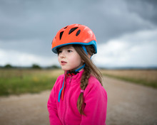 Girl Wearing Orange Cycling Helmet Looking Sideways