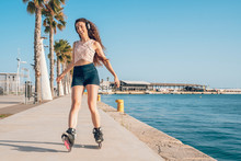 Young Woman Inline Skating On Promenade At The Coast