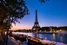 Eiffel Tower By Seine River Against Clear Blue Sky At Sunset, Paris, France