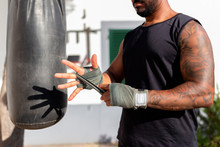 Close-up Of Man Tying Bandage On Hand While Standing By Punching Bag In Yard