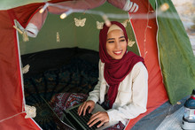 Young Woman Wearing Hijab Using Laptop In A Tent