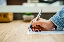 Businesswoman's Hand Writing On Document At Wooden Desk In Modern Office