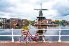 Netherlands, North Holland, Haarlem, Bicycle Parked Along Railing Of Canal Bridge With De Adriaan Windmill In Background