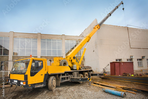 Canvas Print Big Power Mobile Crane on a road and tower crane in construction site