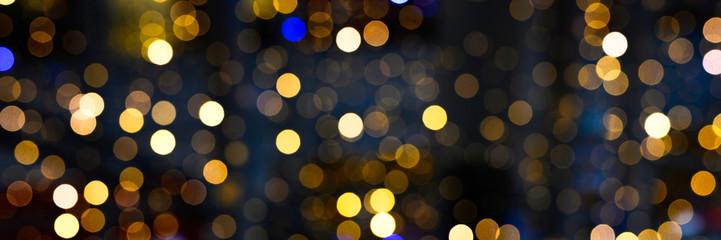 blurred glowing lights of garlands of golden color, bokeh. banner