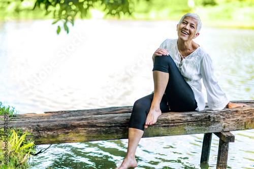 Fotografie, Obraz Beautiful mature woman enjoying peace and tranquility of the nature