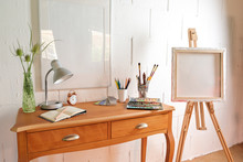 Small Workplace Of An Artist With Crayons, Sketchbook, Watercolour Box And Brushes On A Table And An Easel Against A Rough White Painted Wall, Copy Space
