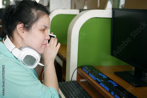 Asian young blind person woman with headphone using smart phone with voice assistive technology for disabilities persons in workplace with computer and braille display on table Fototapeta