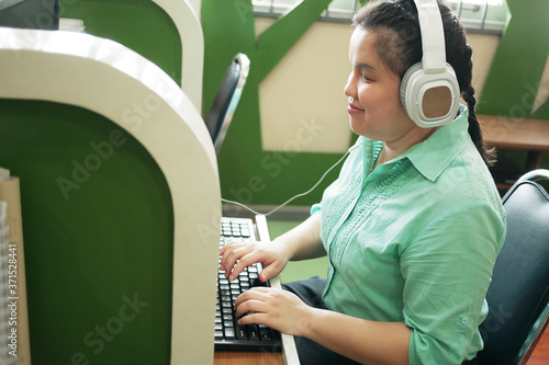 Fotografie, Tablou Disability young blind person happy woman in headphone typing on computer keyboard working in creative workplace office