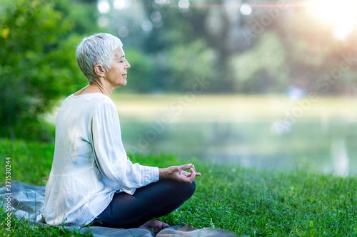 Obraz Senior woman meditating by the water - fototapety do salonu