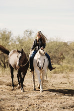Woman Riding Bareback On Horse Shows Farm And Ranch Lifestyle With Horses Close Up Ponying Through Rural Texas Field.
