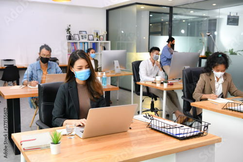 Asian office workers wearing face masks working in new normal office and doing s Canvas