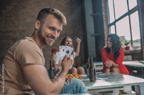 Smiling man cheating with an ace card while playing cards Fototapeta
