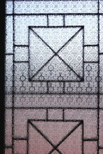 Vintage Clear Embossed Window Glass With Geometric Security Grille Visible In Shadow Behind