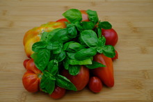 Some Basil And Some Freshly Picked Tomatoes On A Table