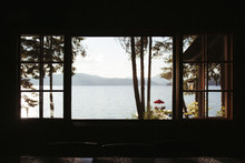View Of Lake And Mountains And Dock Sunny Through The Silhouette Of A Window