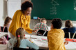 Happy black teacher and elementary students using digital tablet in the classroom.