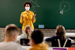 African American elementary teacher wearing face mask while giving a lecture to her students in the classroom.