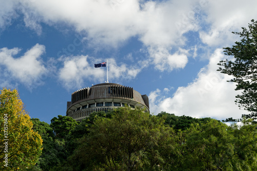Photo The Beehive above the treeline - New Zealand parliament building with flag flying on a sunny day