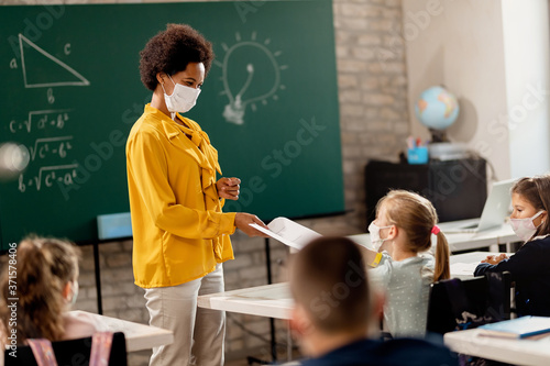 Fotografie, Obraz Happy black teacher giving exam paper to her student while wearing protective face mask in the classroom