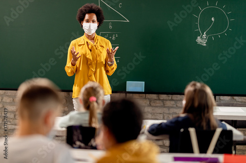 Fotomural African American elementary teacher wearing face mask while giving a lecture to her students in the classroom