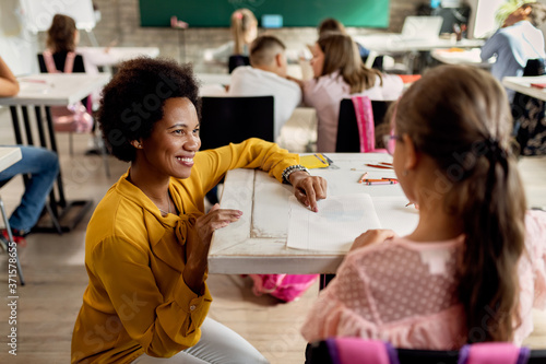 Photo Happy black teacher assisting her student during a class at elementary school