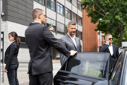 Leinwand Poster Bodyguards Protecting Businessman Opening Car Door